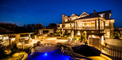 Monmouth County custom home backyard with pool shown at night