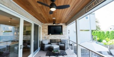 Outdoor lounge with ceiling fan and TV in NJ custom home