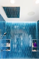 Shower niches in blue tile bathroom of custom home
