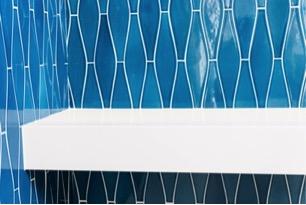 Shower shelf in blue tiled shower in New Jersey custom built home